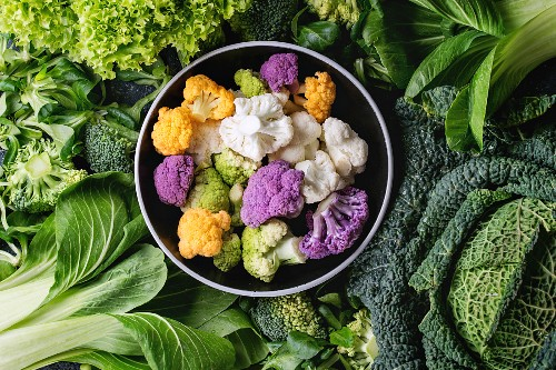 Variety of raw green vegetables salads, lettuce, bok choy, corn, broccoli, savoy cabbage round colorful young cauliflower in black bowl