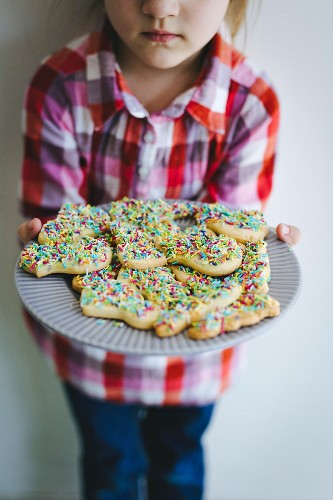 Girl holding plate of cookies