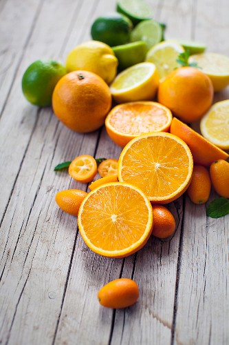 Fresh citrus fruits, whole and halved, on a wooden board
