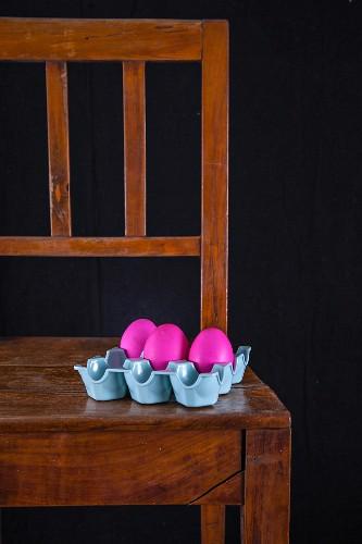 Pinke Ostereier im Eierkarton auf Holzstuhl