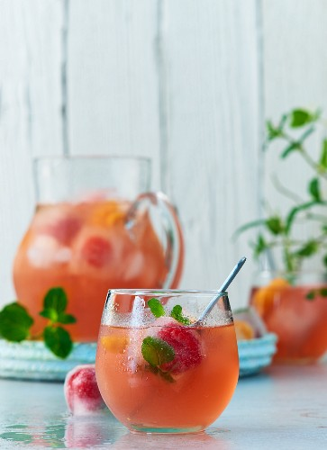 Fruity summer punch with pomegranate juice, mineral water, mint, ice cubes, and frozen berries