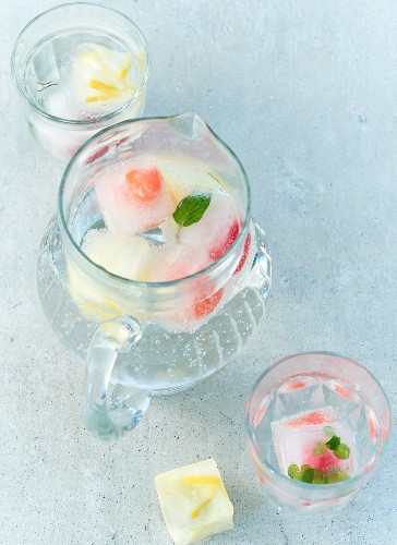 Mineral water with summer fruit ice cubes in a jug