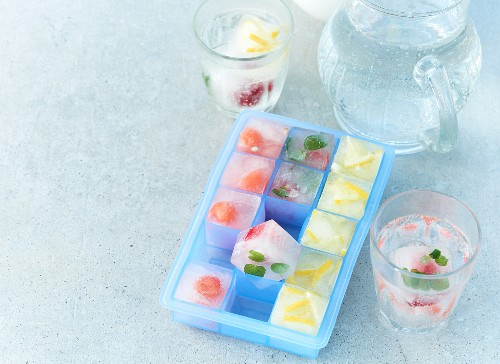 Summer fruit ice cubes in an ice cube tray and in glasses