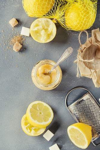 Jar of homemade lemon curd with spoon, whole and sliced lemons, sugar, grater and zest over gray blue stone background