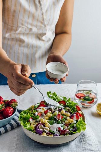 A woman drizzling yogurt dressing over a fresh strawberry pasta salad