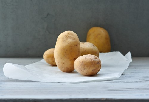 Several cooking potatoes on a piece of paper