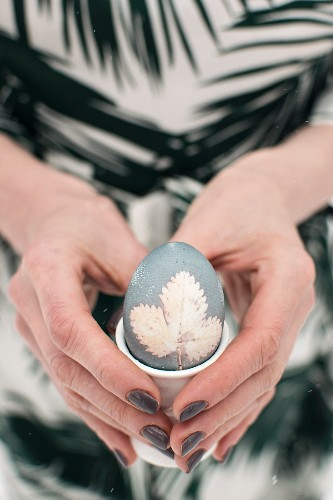 A woman holding an Easter egg in an egg cup