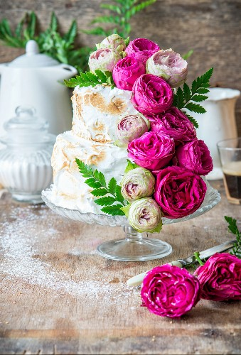 A rose water layer cake with meringue and pink roses