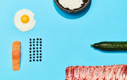 Zutaten für koreanische Gerichte (Lachs, Spiegelei, Reis, Gurke und Schweinerippchen)