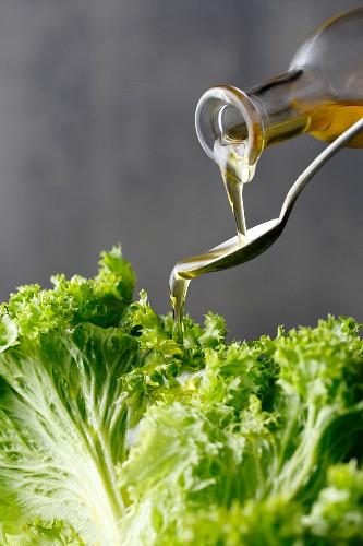 Olive oil being poured over a fresh lettuce leaf