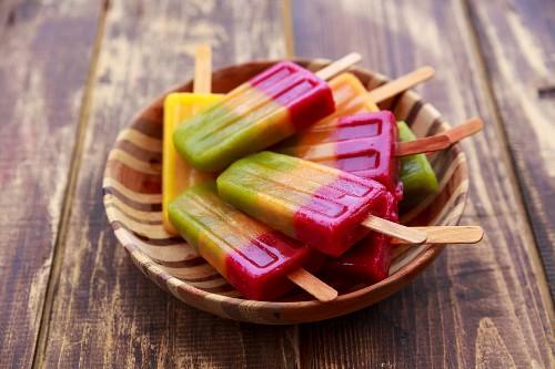 Selbstgemachtes buntes Smoothie-Eis am Stiel (Kiwi-, Orangen-, Zitronen-, Beerensmoothie)