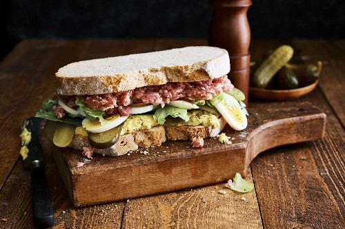 A ground pork sandwich with onion mustard, gherkins and hard-boiled egg