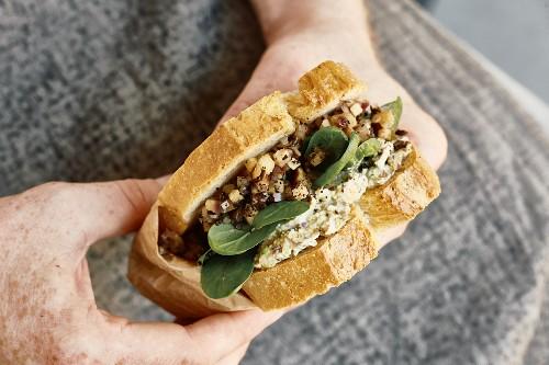 A white bread sandwich with aubergine, spinach and pistachio spread