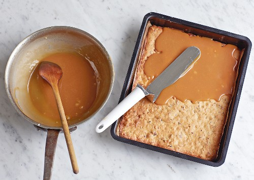 Spreading caramel onto a biscuit base