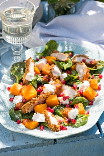 Chicken salad with pumpkin, goat's cheese, spinach and pomegranate dressing