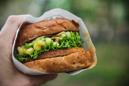 A hand holding a veggie burger with corn, lettuce and guacamole
