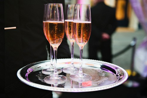 Four glasses of rosé champagne on a silver tray