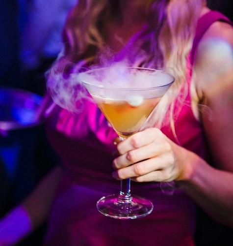 Frau hält Cocktailglas mit weißem Rauch in einem Nachtclub