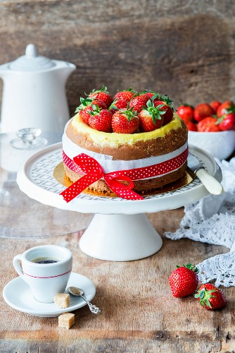A small vanilla cheesecake decorated with strawberries and red ribbon