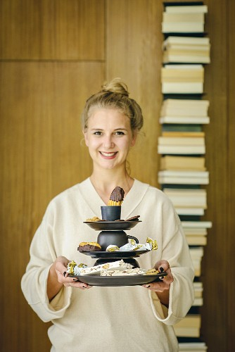 Young woman holding hand-made cake stand made from plates and cups