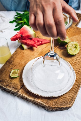 A woman dipping a margarita glass into salt
