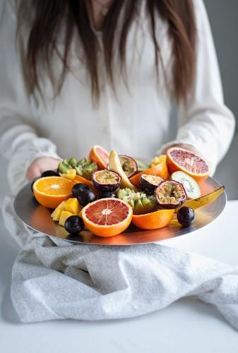 A woman serving a fruit platter