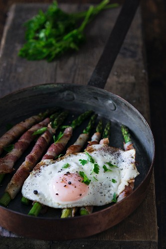 Bacon-wrapped green asparagus in a pan with a fried egg