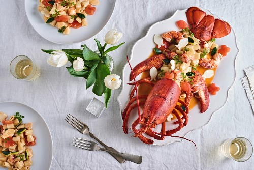 Lobster with rigatoni on a table decorated with a vase of tulips (seen from above)