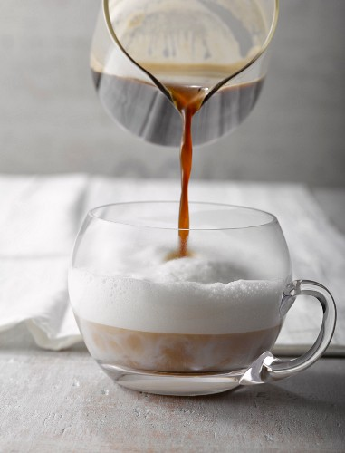 A milk coffee in a glass cup