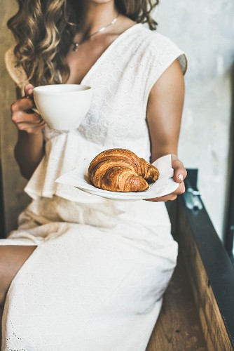 Young blond woman in white dress holding fresh croissant in plate and cup of cappuccino in cafe