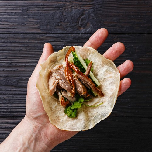 Peking Duck with cucumber, green onions and cilantro in roasted wheaten chinese pancakes in male hand