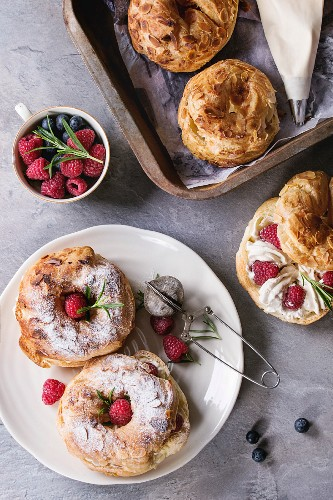 Filling and empty homemade choux pastry cake Paris Brest with raspberries, almond, sugar powder, rosemary on plate and oven tray with berries