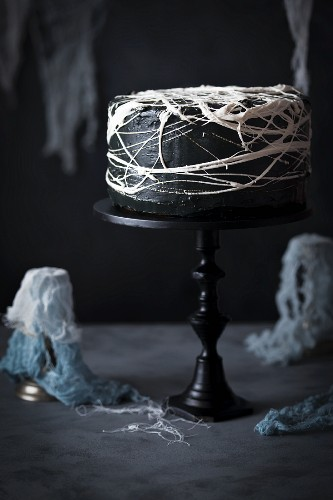 Halloween cake with black frosting and marshmallow spider's web