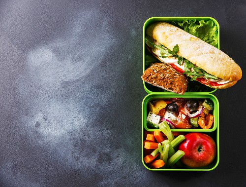 Take out food Lunch box with Tuna and egg Sandwich, Greek salad and vegetables on blackboard background