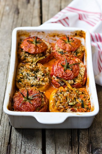 Gemista, tomatoes and yellow bell peppers stuffed with rice and herbs in tomato sauce