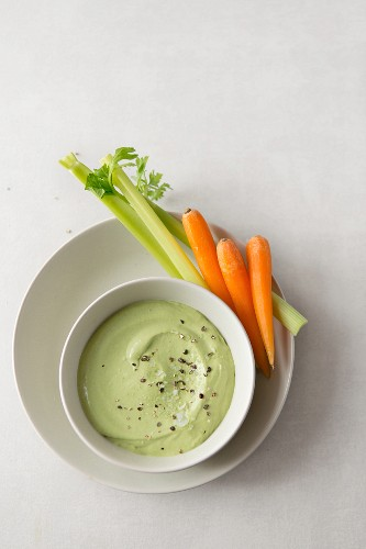 A tahini and coriander dip with pepper, sea salt flakes and carrot and celery sticks