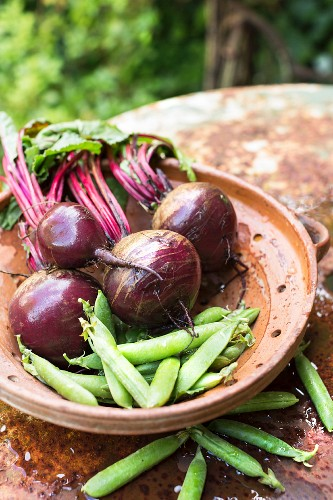 Beetroot and peas in a clay dish on a rusty table outdoors