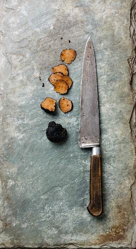 Sliced Black truffle and kitchen knife on stone shale slate background