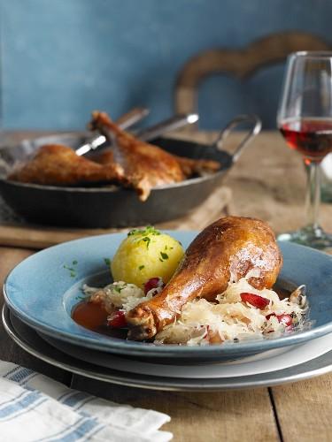 A goose leg with sauerkraut and a potato dumpling