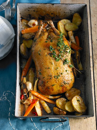 Herb duck in an oven dish with vegetables