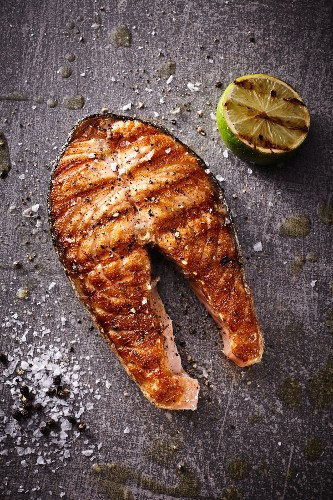 A grilled salmon steak with half a lime, salt and pepper