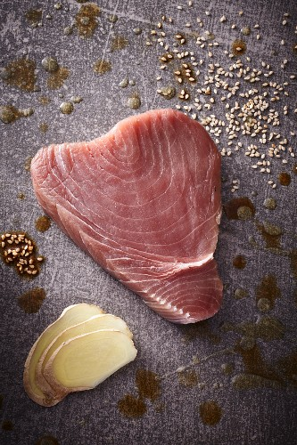 A raw tuna steak with sesame seeds and slices of ginger