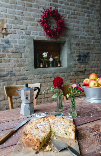 Apple cake and an espresso pot on a rustic wooden table