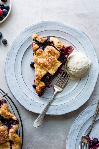 A slice of berry pie with vanilla ice cream on a plate