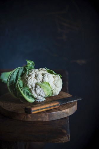 Cauliflower and a knife on a wooden table