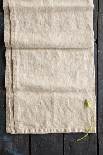 A wild garlic flower on a linen cloth (seen from above)