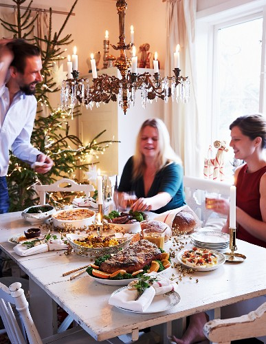 A family sitting around a table set for Christmas dinner