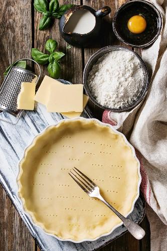 Dough for baking quiche tart in ceramic baking form ready for bake