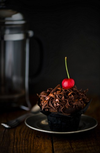 A chocolate cupcake with a cherry