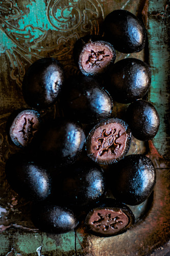 Black nuts on an antique wooden tray